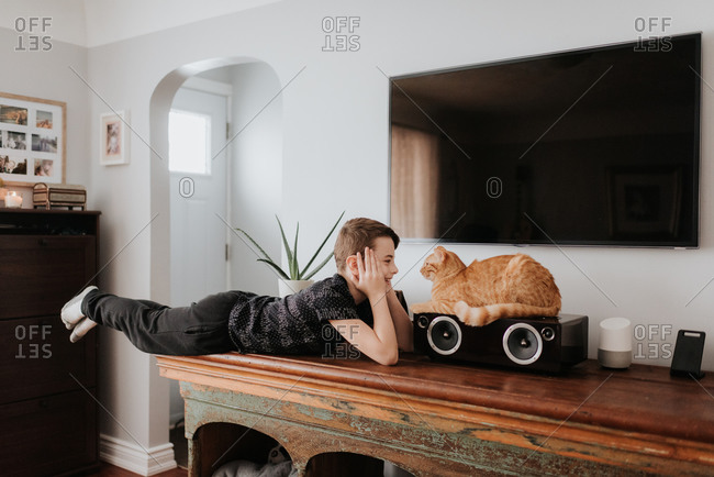 Boy staring at cat on cabinet