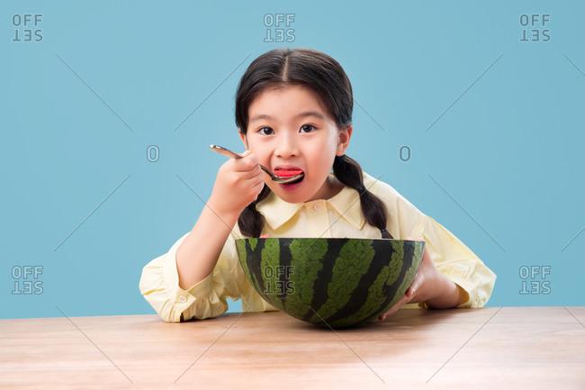 Lovely little girl eating watermelon