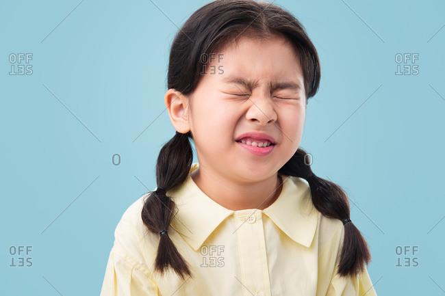 Little girl scrunches up her face