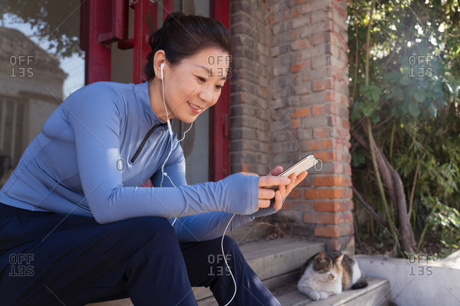 Middle-aged woman sitting on the steps and listening to music