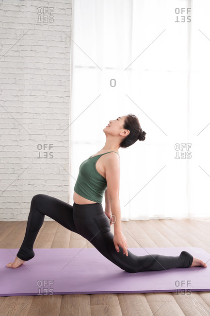 Middle-aged woman doing yoga indoors
