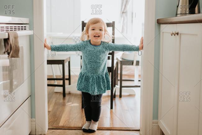 Female toddler standing in kitchen doorway, portrait