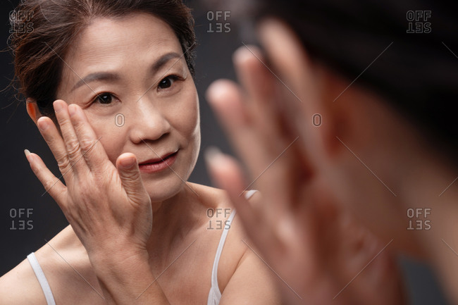 Middle-aged woman in front of woman and applying skincare
