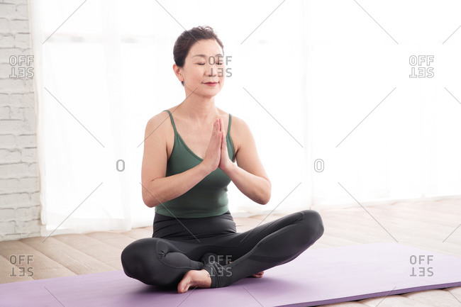 Middle-aged woman meditating on yoga mat