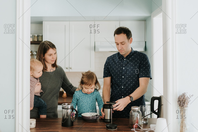 Mid adult couple with toddler daughter and baby son preparing food at kitchen table