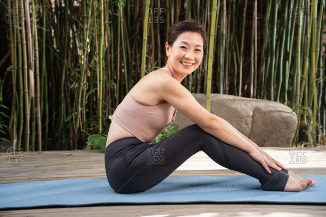 Middle-aged woman sitting on yoga mat