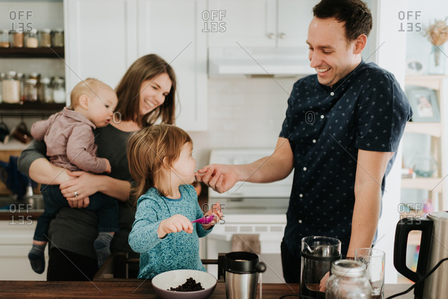 Mid adult couple with toddler daughter and baby son at kitchen table