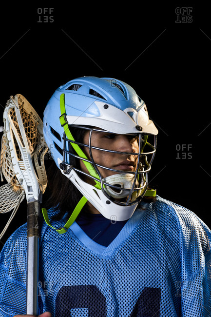 Young male lacrosse player with lacrosse stick, portrait against black background