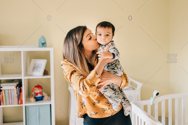 Mother kissing baby son in nursery, portrait