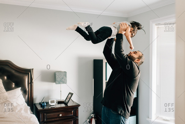 Girl being held up by father in bedroom