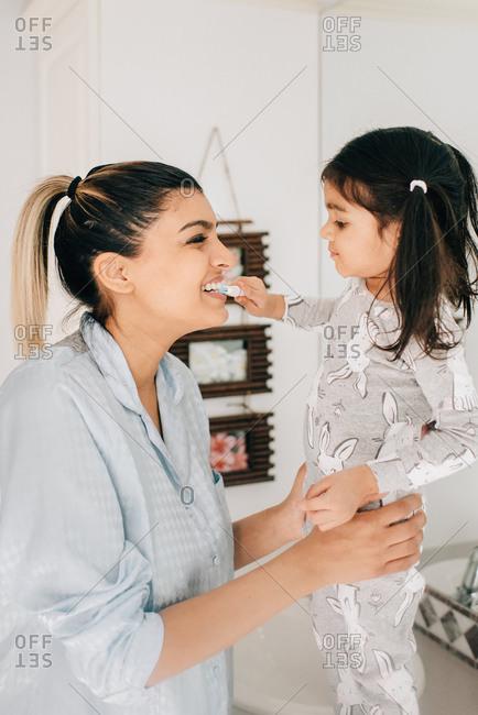 Girl brushing mother's teeth in bathroom