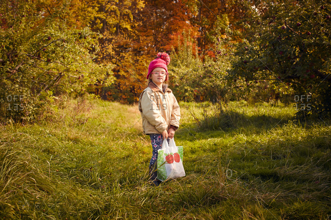 Girl with bag of fresh picked apples in orchard