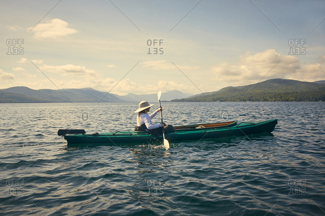 Woman paddling kayak, Adirondacks, Lake George, New York, United States