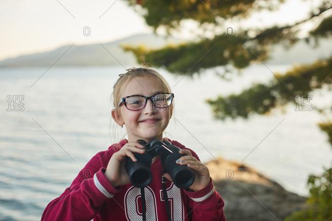 Girl with binoculars looking far
