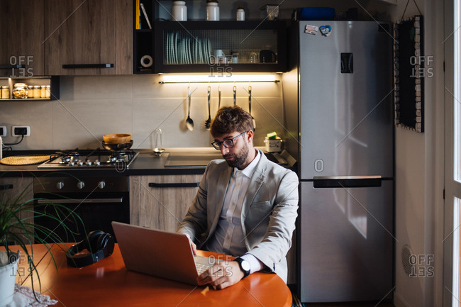 Mid adult man sitting at kitchen table typing on laptop