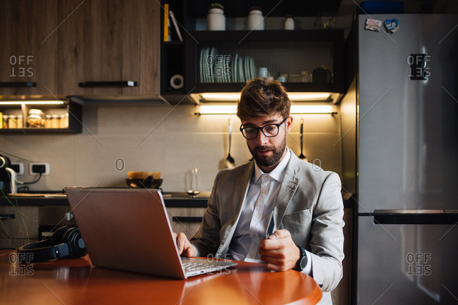 Mid adult man sitting at kitchen table with laptop and credit card