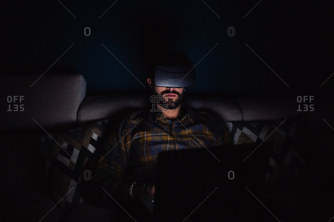 Bearded mid adult man sitting on sofa in darkness looking through virtual reality headset