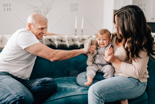 Mother and father on sofa with baby daughter playing with soft toy