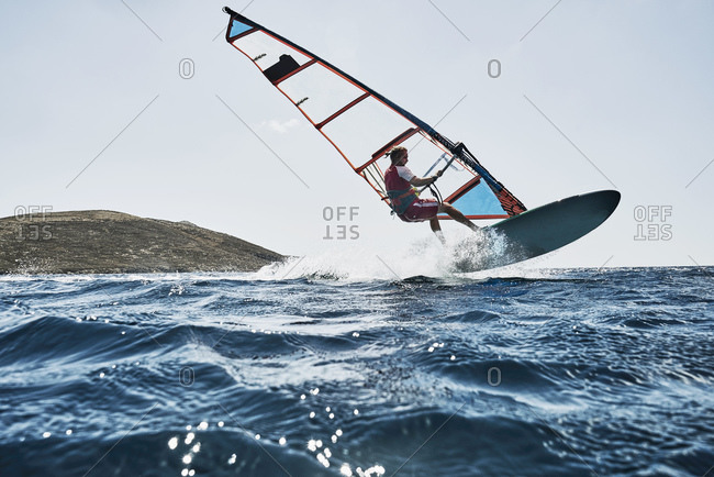 Young man mid air while windsurfing ocean waves, Limnos, Khios, Greece