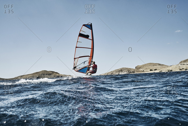 Young man leaning back windsurfing ocean waves, side view, Limnos, Khios, Greece