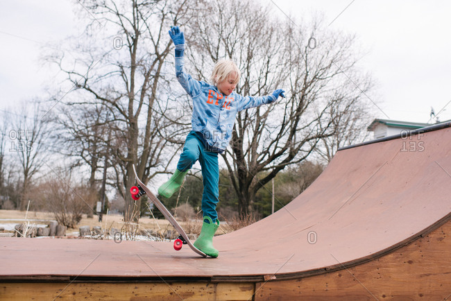 Boy on rural skateboard ramp practicing skateboarding trick