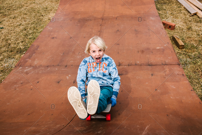 Boy sitting and skateboarding backwards down wooden skateboard ramp, portrait