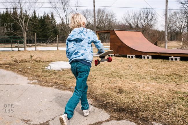 Blond boy carrying skateboard toward rural skateboard ramp, rear view