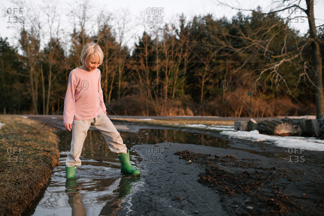 Boy stepping ankle deep in rural meltwater puddle