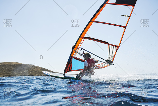 Young man leaning back windsurfing ocean waves, surface level rear view, Limnos, Khios, Greece