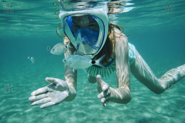 Underwater view of girl snorkeling, looking at fish, Limnos, Khios, Greece