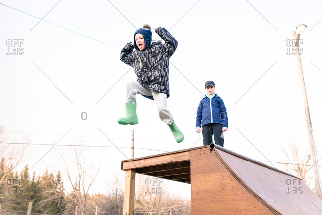 Girl watching brother jump from top of skateboard ramp
