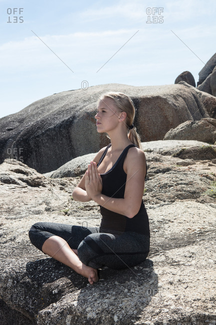Young woman practicing lotus yoga pose on beach rock, Cape Town, Western Cape, South Africa