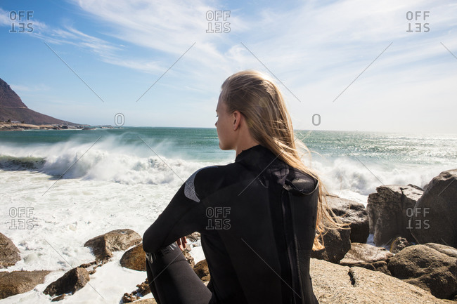 Young female surfer with long blond hair sitting on beach rock, rear view, Cape Town, Western Cape, South Africa