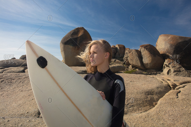 Young female surfer with flyaway hair looking out from beach rock, Cape Town, Western Cape, South Africa