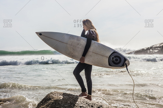 Young female surfer stepping onto beach rock, Cape Town, Western Cape, South Africa