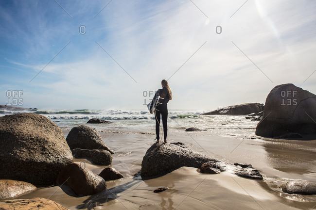 Young female surfer looking out from beach rock, rear view, Cape Town, Western Cape, South Africa