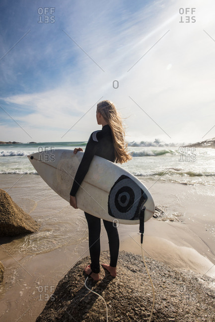 Young female surfer looking out from beach, rear view, Cape Town, Western Cape, South Africa