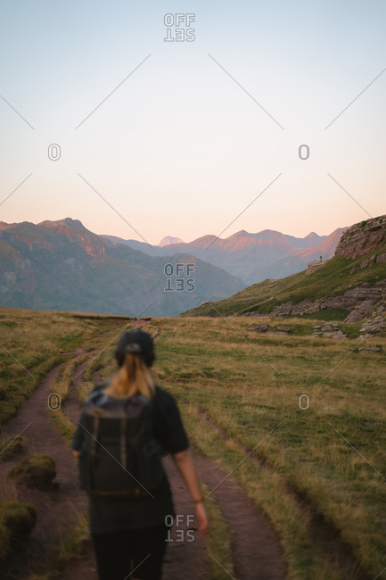 Lonely girl hiking in Spanish Pyrenees during sunset