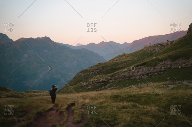 Caucasian girl standing on a mountain path during a hike in Pyrenees
