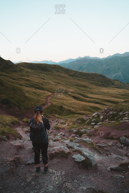 Blonde girl taking a photo of the landscape with her phone from the top of a steep hill