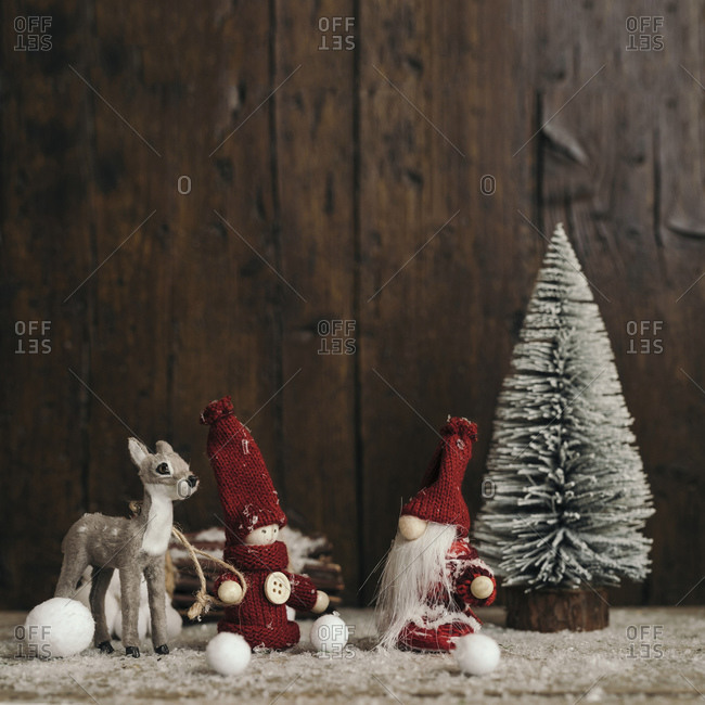 Front view of Santa Claus, gnome, and reindeer walking in a snowy scenery