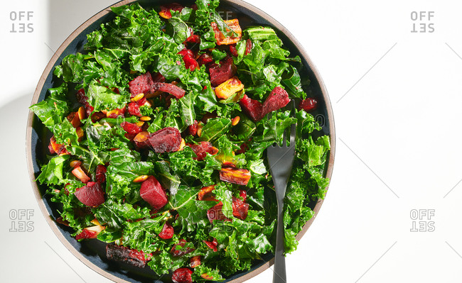 A healthy kale salad with beetroot, pumpkins seeds and cranberries on a white background