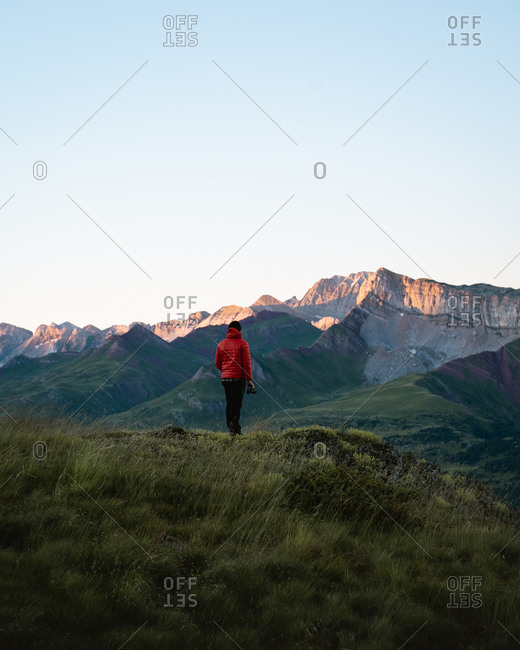Young man wearing a red down jacket watching a peaceful sunrise