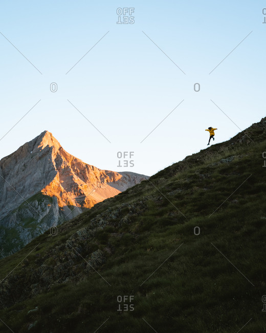 Young man wearing yellow jacket running down a steep hill in Pyrenees