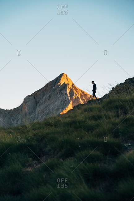 Silhouette of a young hiker during sunrise in the mountains