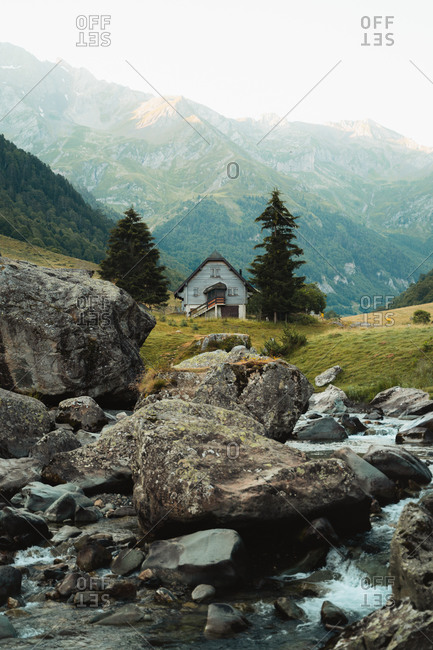 Wooden cabin between two pine trees, close to a river in French Pyrenees