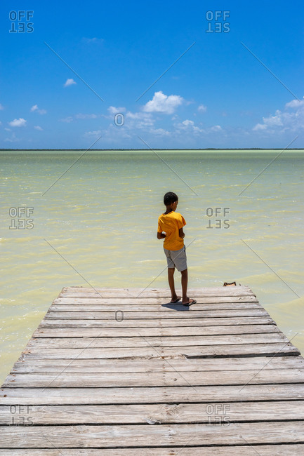 America, Caribbean, Greater Antilles, Dominican Republic, Oviedo, Laguna de Oviedo, boy stands on the jetty at the Laguna de Oviedo salt water lake
