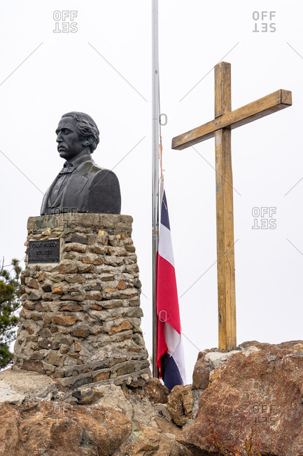 August 18, 2019: Greater Antilles, Dominican Republic, Jarabacoa, Manabao, Parque Nacional Jose Armando Bermudez, Pico Duarte, summit cross, statue and Dominican flag on the summit of Pico Duarte