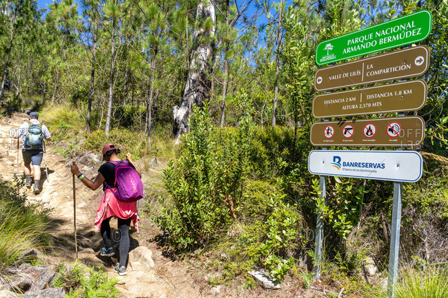 August 18, 2019: Greater Antilles, Dominican Republic, Jarabacoa, Manabao, Parque Nacional Jose Armando Bermudez, Pico Duarte, hikers pass a sign on the climb to Pico Duarte