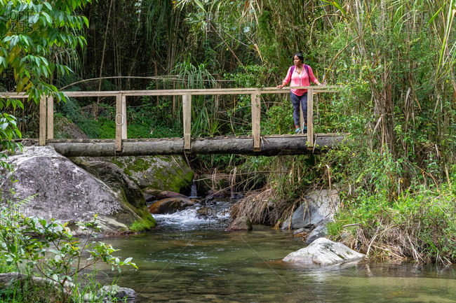 Greater Antilles, Dominican Republic, Jarabacoa, Manabao, Parque Nacional Jose Armando Bermudez, Pico Duarte, Woman stands on a wooden bridge over the Yaque del Norte and looks out into the landscape